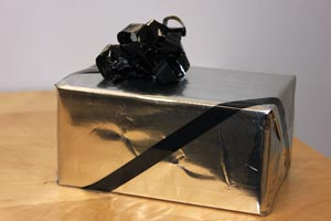 This gift is wrapped in a cleaned chip bag, turned foil-side out and adorned with a VHS ribbon.
